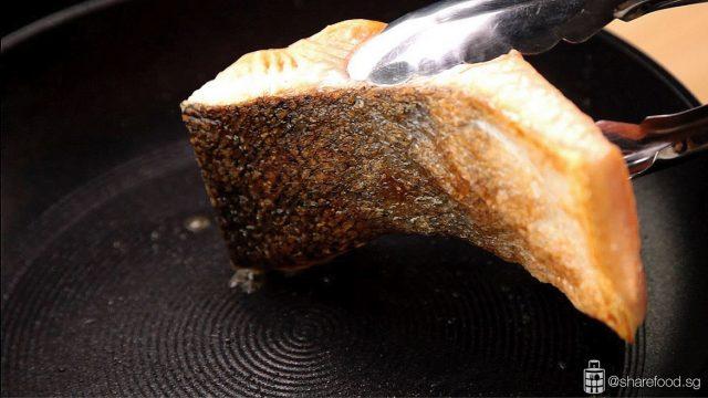 pan fried salmon flipping in a pan