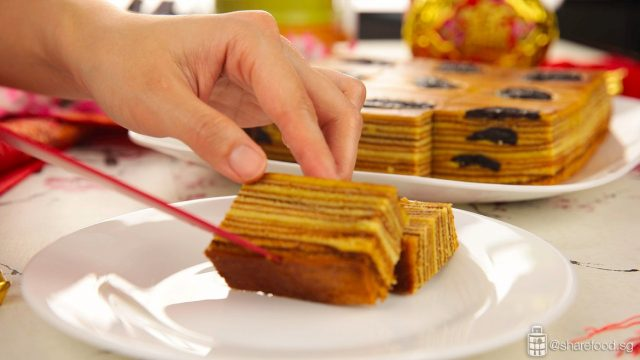 placing a piece of prune kueh lapis into a white plate
