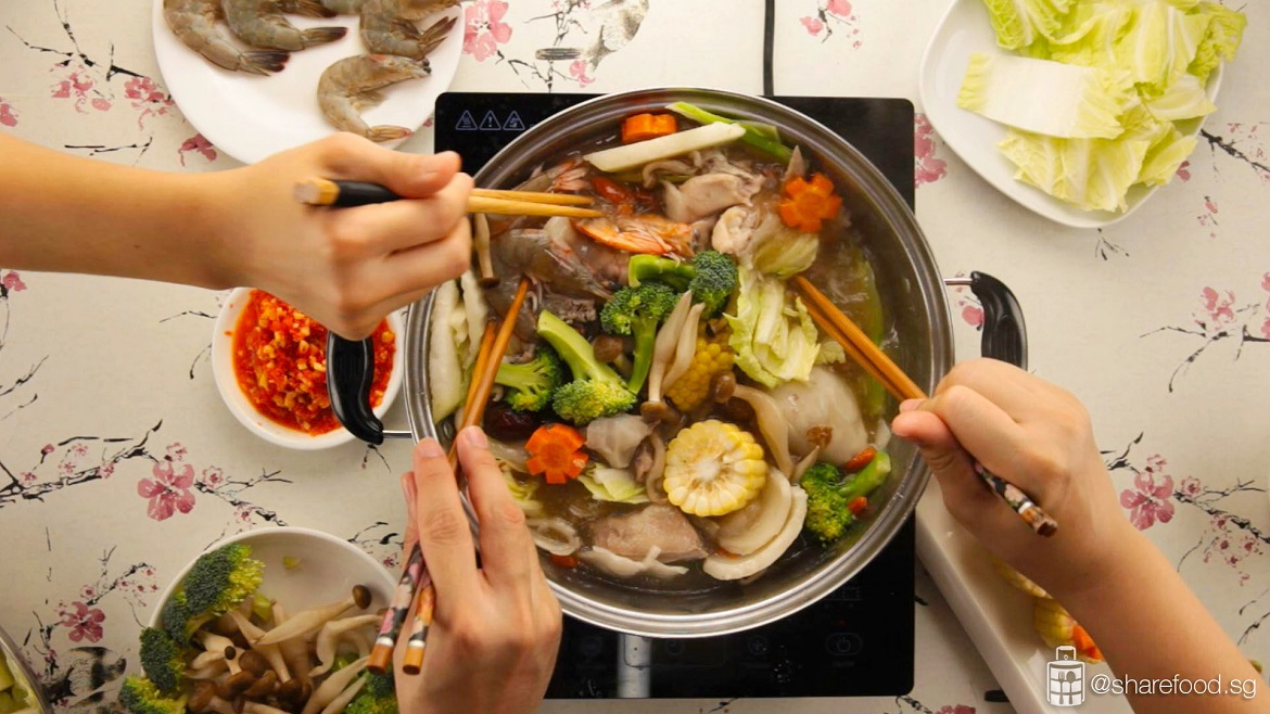 multiple hands with chopstick having coconut chicken steamboat