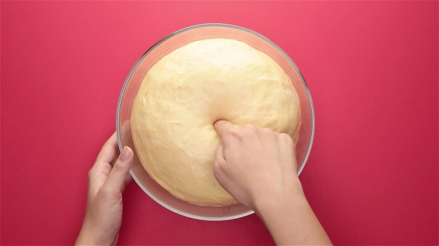 Poke the dough to release air