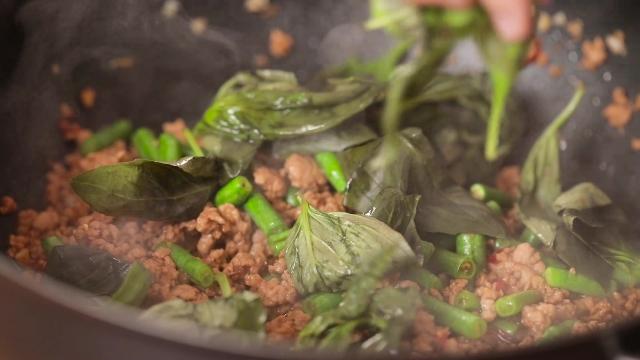 Adding basil leaves to frying pan