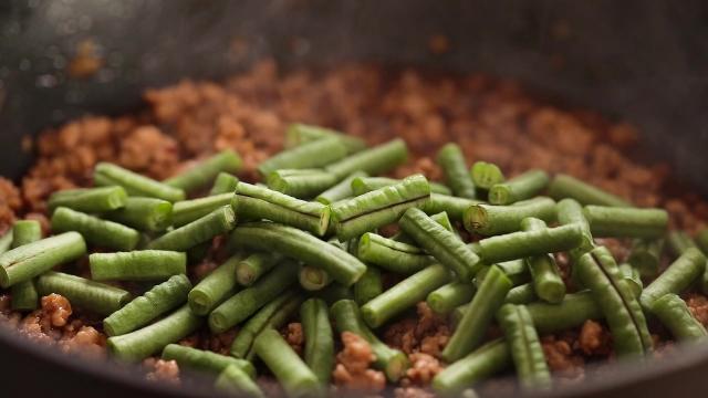 Adding long beans to frying pan