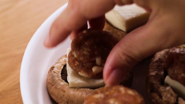 Putting pork balls on tofu on top of portobello mushrooms