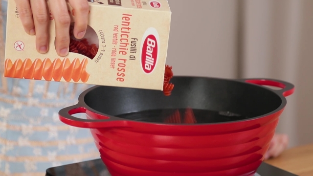Pouring Barrila red lentil pasta into pot