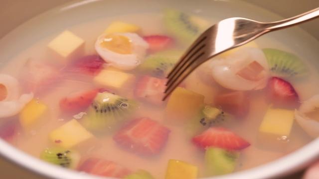 Score mixed fruit agar agar with a fork