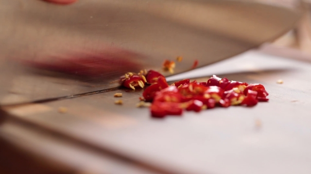 Slicing red chilli padi with a knife