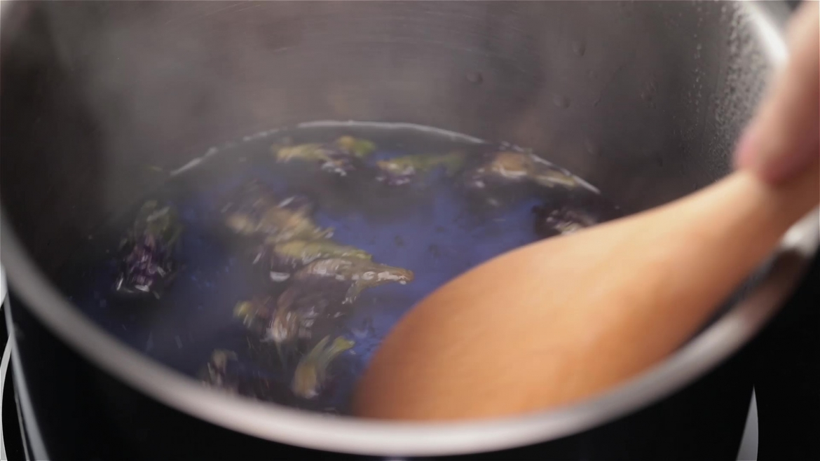Boiling blue butterfly pea flower and stirring with a wooden spatula