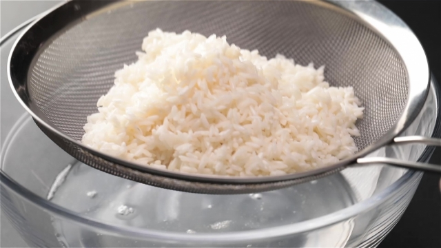 Draining white glutinous rice with a metal sieve