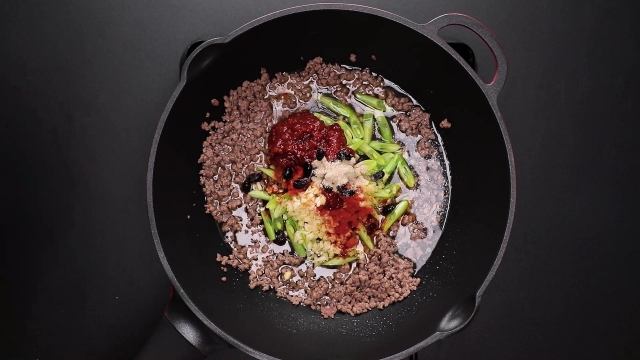 Stir frying beef, french beans, and chilli bean paste ingredients in frying pan