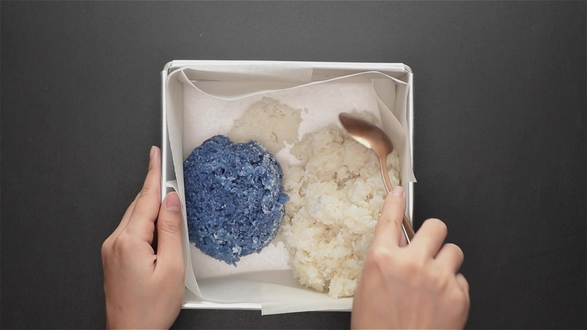 Mixing blue and white rice in baking tin