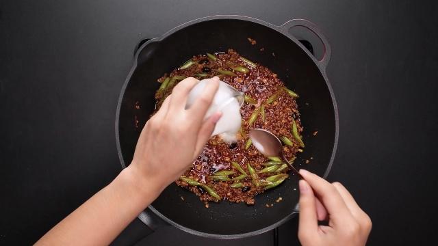 Pouring cornflour mixture to spicy bean sauce