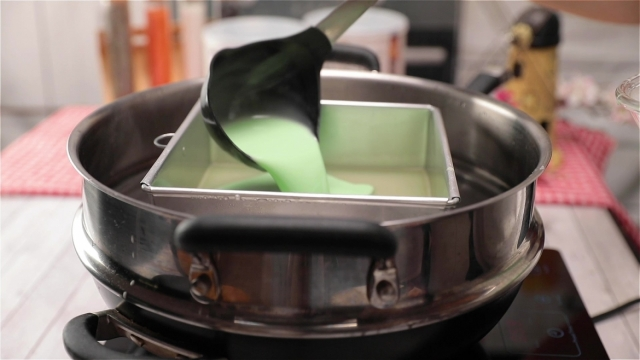 Pouring green kueh lapis batter into baking tin