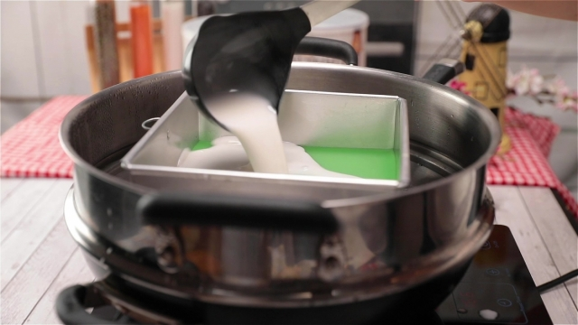 Pouring white kueh lapis batter into baking tin