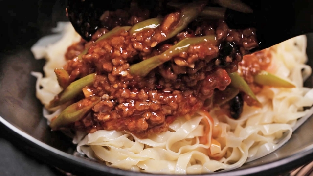 Scooping spicy bean paste sauce and minced beef onto meepok noodles