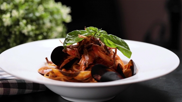 Seafood spaghetti with fried onions and basil