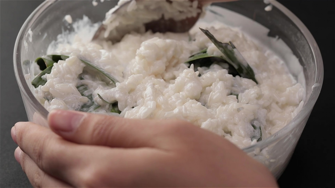 Stuffing pandan leaves into white rice and thick coconut milk
