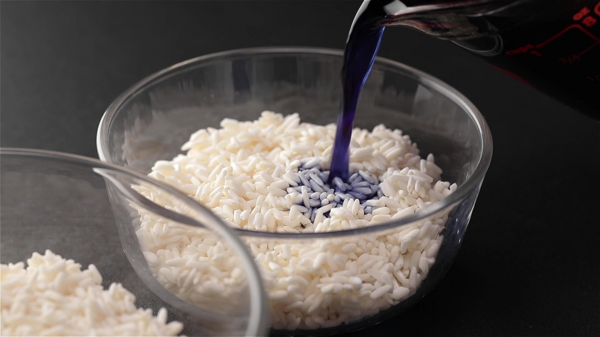 Pouring blue blutterfly pea flower water into glutinous rice