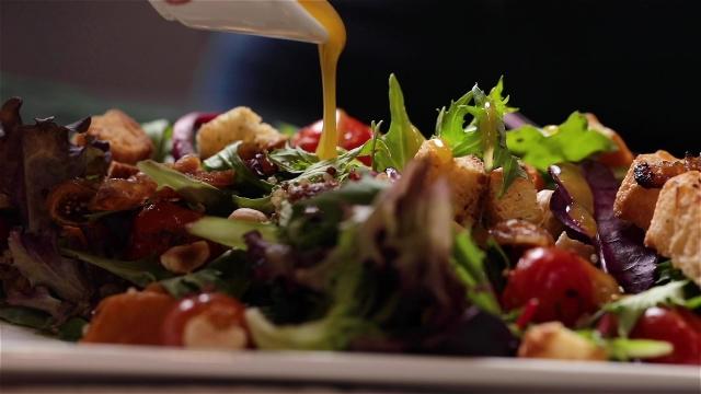 Drizzling sauce on Zazz salad
