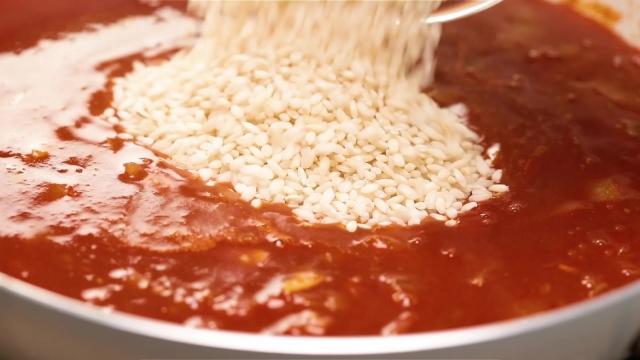 Adding carnaroli rice to pan full of tomato sauce