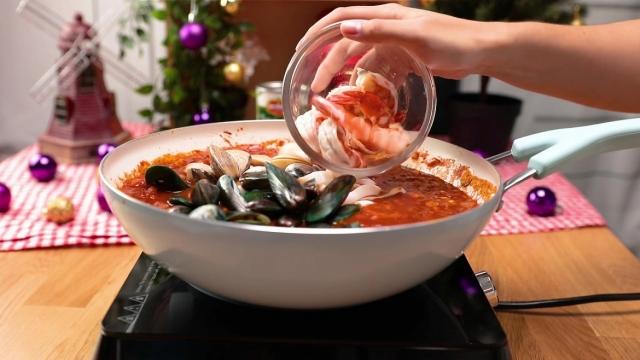 Adding seafood to pan ful of tomato sauce