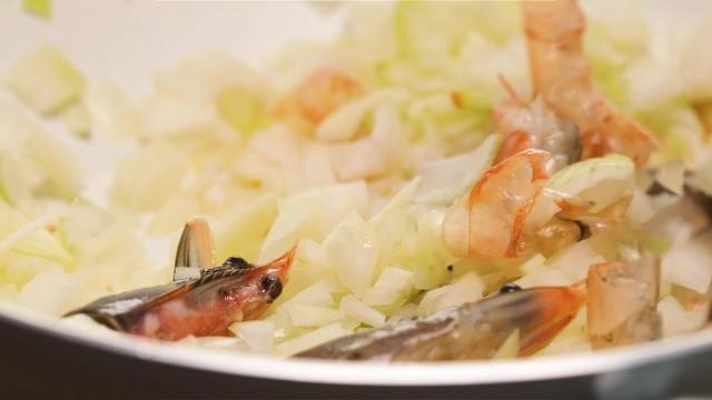 Frying prawn head, shells, and onion