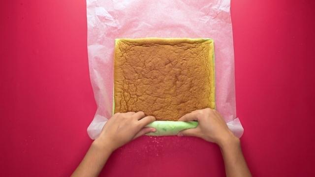 Rolling up pandan swiss roll cake with baking sheet