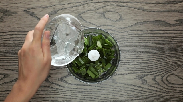 Adding water to food processor with pandan leaves inside