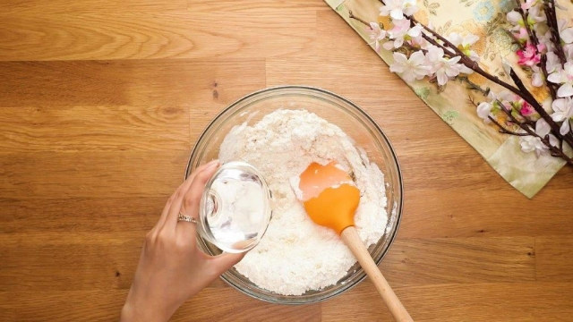Adding water to mixed flour in glass bowl with spatula