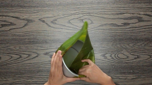 Folding banana leaf down into a round baking tin