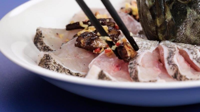Placing cooked mushrooms onto sliced fish with chopsticks