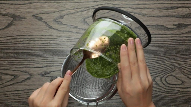 Pouring blended pandan pulp from food processor into metal strainer