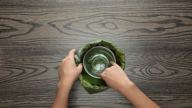 Pushing banana leaf into wrapped baking tin with a circular bowl