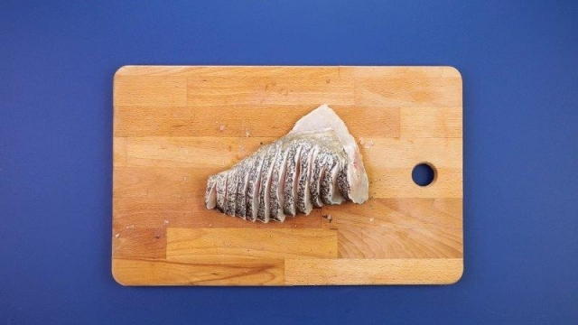 Sliced fish in peacock style on wooden chopping board