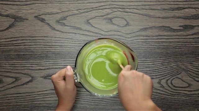 Stirring green pandan batter in measuring jug