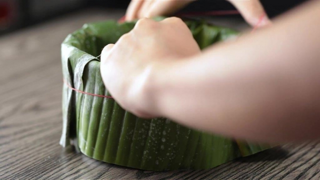 Tying rubber band around banana leaves wrapped around baking tin