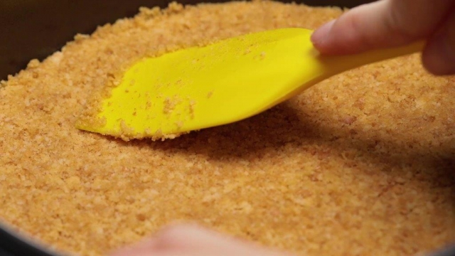 Pressing cheesecake biscuit base with a spatula