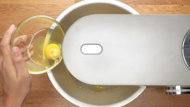 Adding eggs to mixing bowl