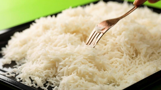 Fluffing basmati rice on a tray with a fork