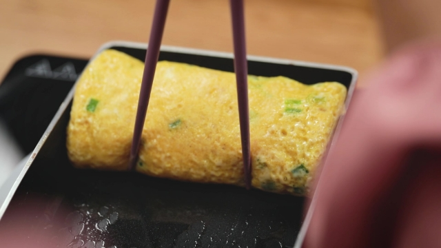 rolled tamagoyaki in pan with chopsticks