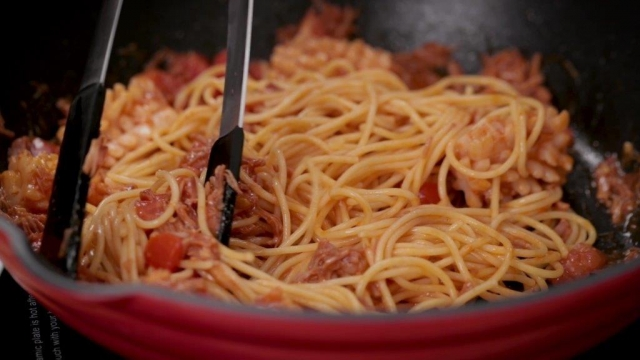 Stir frying spaghetti in a pan with tongs