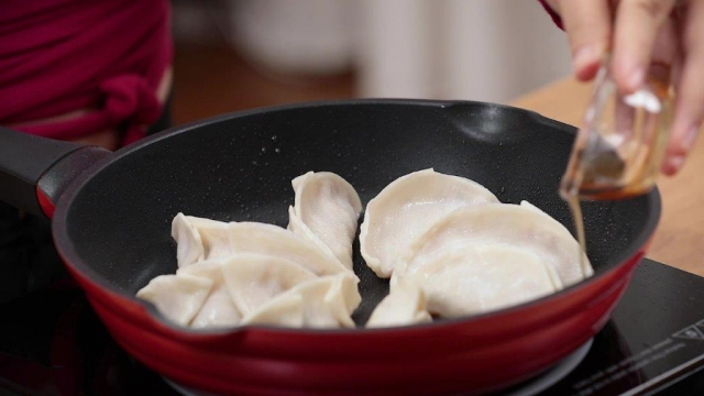 pouring sesame oil to gyoza in pan