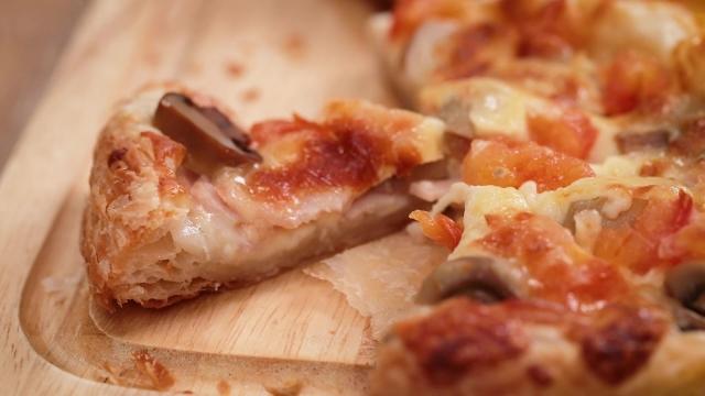 Frozen prata pizza slices on wooden board