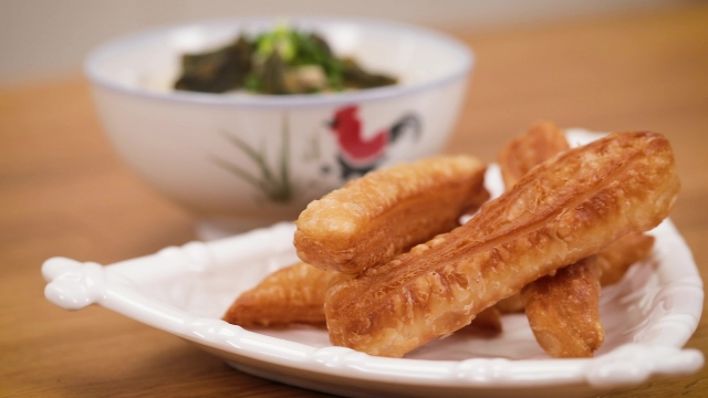 a plate of frozen prata youtiao with century egg chicken porridge
