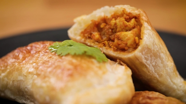 Close up of prata curry puff with chicken and potatoes