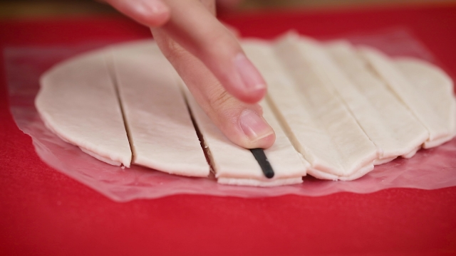 pressing chopstick on frozen prata strips to make youtiao shape