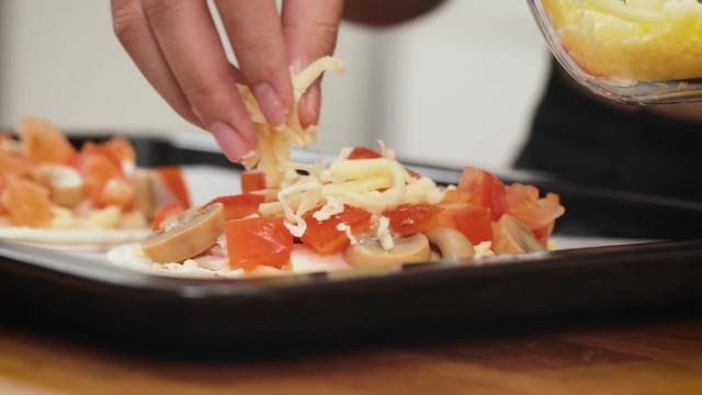 sprinkling prata pizza with mozzerella cheese