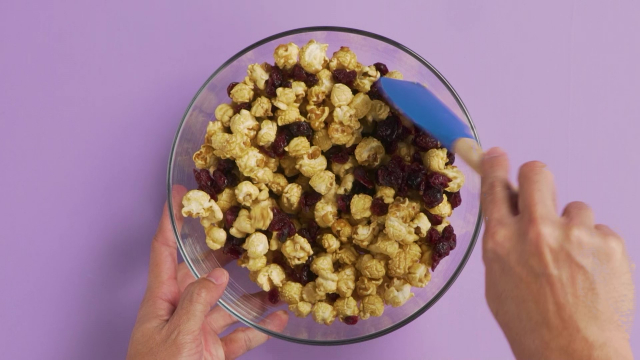 Tossing popcorn and dried cranberries in a bowl