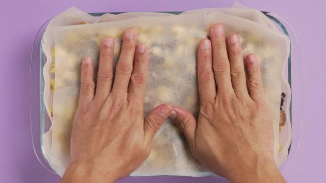 Hands pressing on baking paper covered popcorn bar