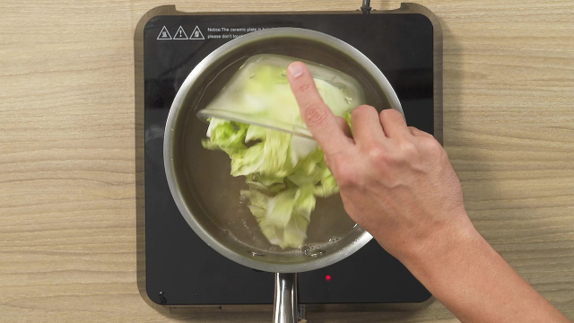 Adding sliced cabbage to boiling soup in pot