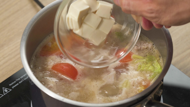 Adding tofu in glass bowl to boiling soup